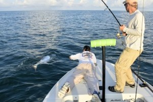 Dave Reinhart, from MA, battles a tarpon while fishing the coastal gulf with Capt. Rick Grassett.